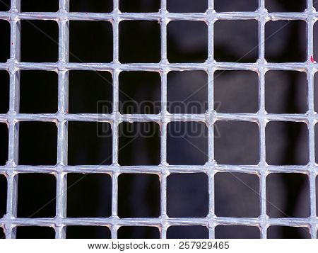 Silver Metallic Grating Of Squares On A Black Background Of The Waters Of A River