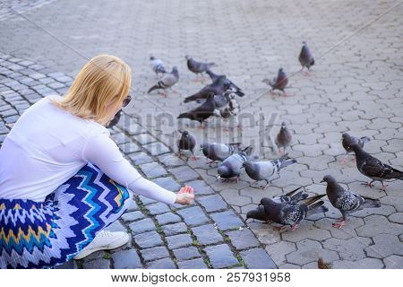 Woman tourist or citizen toss crumbs for pigeons. Girl blonde woman relaxing city square and feeding pigeons. Girl feeding dove birds. Group doves on city square waiting treats. Share generosity poster