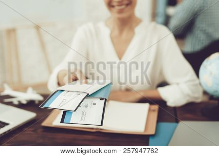 Travel Agent Holding Tickets In Travel Agency. Smiling Woman In Office. Consultant In Travel Office.