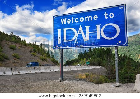 LOOKOUT PASS, IDAHO, USA - September 1, 2018: Traffic drives past the Welcome to Idaho sign on Interstate 90 at the Idaho - Montana border