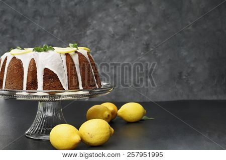 Whole Lemon Cream Cheese Bundt Cake With Slices Of Fresh Lemons And Mint On Top. Extreme Shallow Dep
