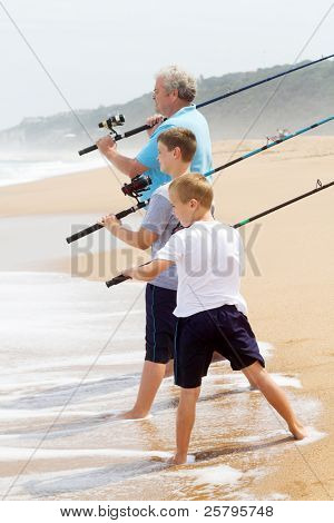 grandpa took his grandsons fishing on beach: ready to cast the fishing line