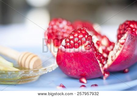 A Beautiful View Of An Open Ripe Pomegranate Fruit With Pomegranate Seeds Seen. Apple Slices Dipped