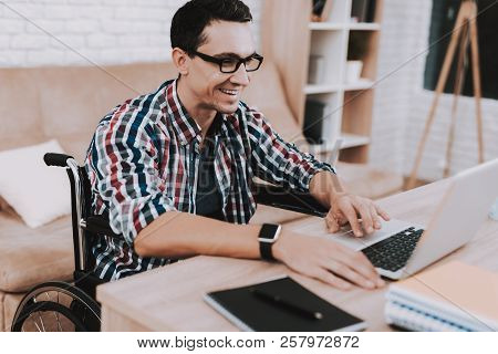 Young Disabled Man On Wheelchair Working At Home. Man On Wheelchair. Disabled Guy. Checkered Shirt.