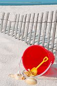 beach bucket and seashells by beach fence poster
