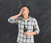 Young guy alcoholic with headache holding bottle of beer, suffering from hangover, dark studio background, alcohol addiction and consequences concept, copy space poster