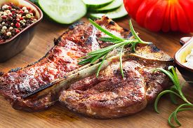 Grilled T-bone Steak With Vegetables On Wooden Background
