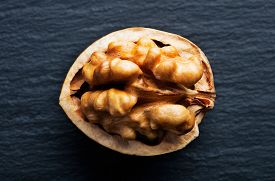 Close-up View Of Cracked Walnut On Slate Background