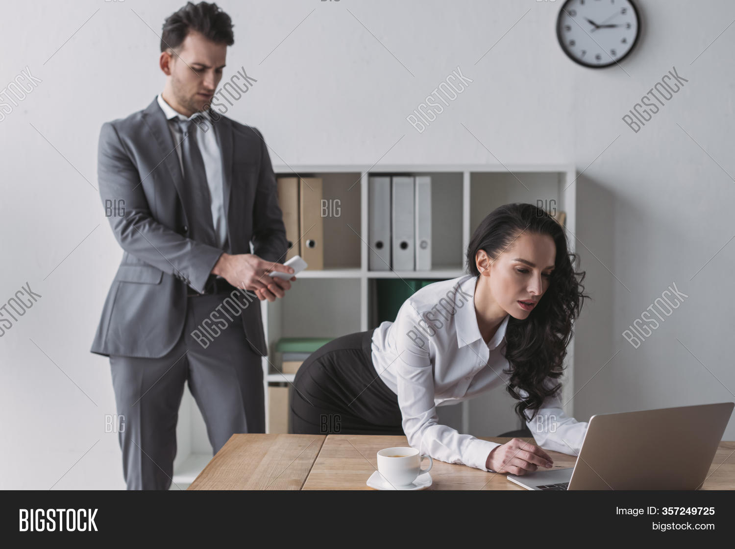 Handsome Businessman Taking Picture Of Buttocks Of Secretary Standing At Workplace