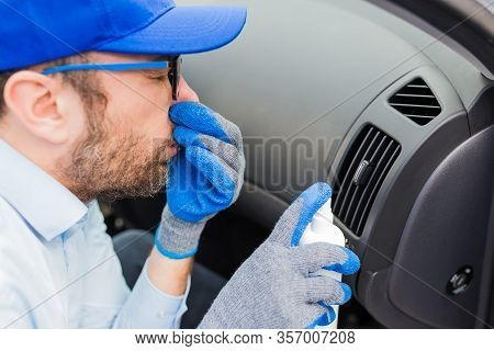 Car Wash Employee Covering His Nose With Hand And Using Bottle With Disinfection Liquid To Neutraliz