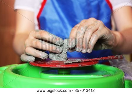 A Child Sculpts His Hands With A Clay Cup On A Potter's Wheel. Hands In Clay. Pottery Male Ceramist