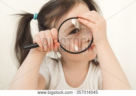 Little Girl Plays A Detective. A Child Examines Something Through A Magnifying Glass. A Girl With Tw