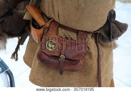 Medieval Leather Historical Waist Bag With A Copper Plaque In The Shape Of A Reindeer Hangs On A Man