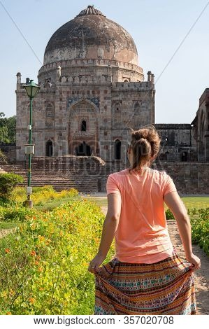 Young Woman Tourist Poses And Holds Her Skirt At The Tomb Of Sheesh Gumbad Tomb In Lodi Gardens In N