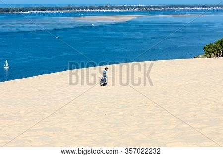 Dune Of Pilat, France - September 10,2018: A Lonely Tourist With A Suitcase On The Dune Of Pilat, Th
