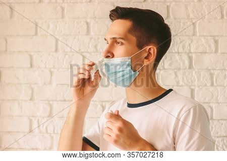 Portrait Of Young Sick Man Using Nasal Drops For Runny Congested Nose. Confident Sick Doctor In Medi