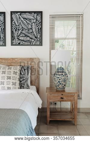 Vertical Photo Of White Interior In Authentic Bedroom With Jalousie On Window, Bed And Lamp On Bedsi