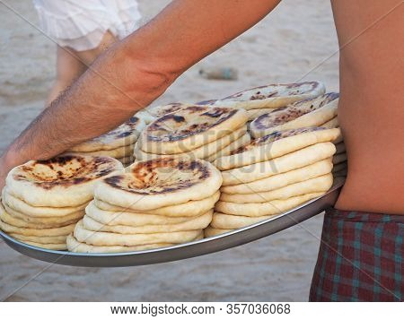 A Man Carries A Tray With Hot Khachapuri. Food Vendor On The Beach.