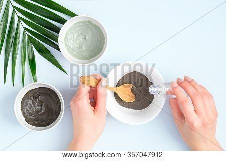 Woman Preparing Cosmetic Clay On Pastel Blue Background. Natural Organic Spa Facial Mask. Flat Lay,