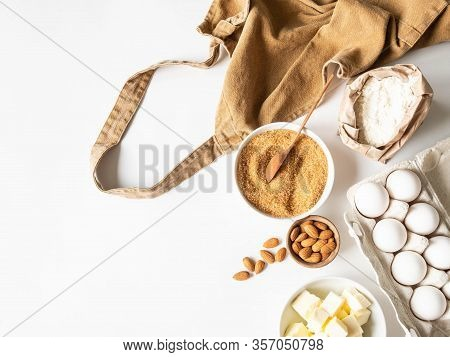 Ocher Apron And Various Baking Ingredients - Flour, Eggs, Sugar, Butter, Nuts On White Background. T