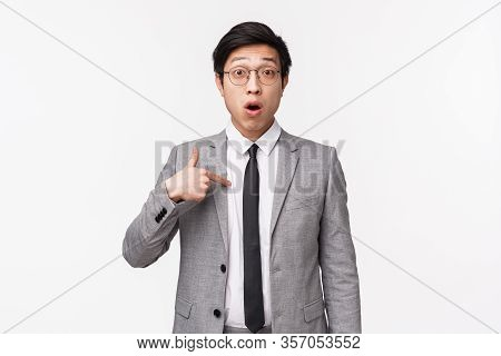 Waist-up Portrait Of Surprised And Confused Asian Businessman, Office Worker Pointing At Himself Wit