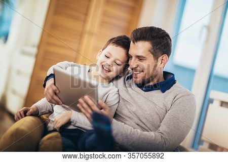 Father And Son Playing On A Tablet At Home, Having Fun
