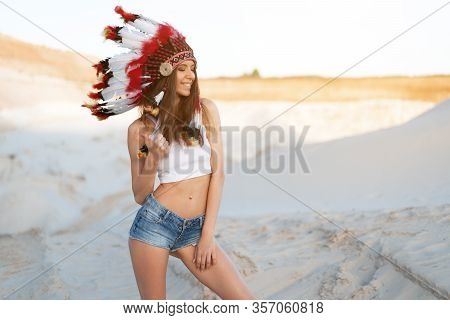A Beautiful Young Caucasian Girl In A White Top And Denim Shorts. On Her Head Wearing An Indian Hat