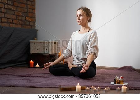 Beautiful Young Caucasian Girl Sitting In Room Lotus Position Meditates. Yoga Classes At Home Medita