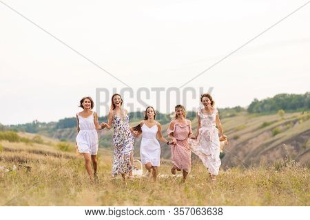 The Company Of Cheerful Female Friends Have A Great Time Together On A Picnic In A Picturesque Place