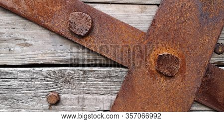 Closeup Texture Of Rusty Iron Sheets Or Slats Bolted To Aged Wooden Planks In Grayish-brown Tone Wit