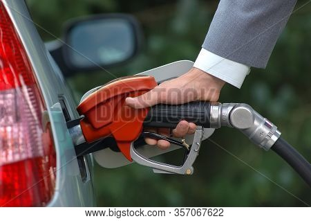 Man Pumping Petrol With Fuel Pump. Vehicle Fueling Facility At Petrol Station. Petrol Price Goes Dow