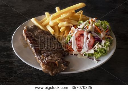 Succulent Portions Of Grilled Fillet Steak Served With Fried Potatoes And Salad On White Plate. Dark