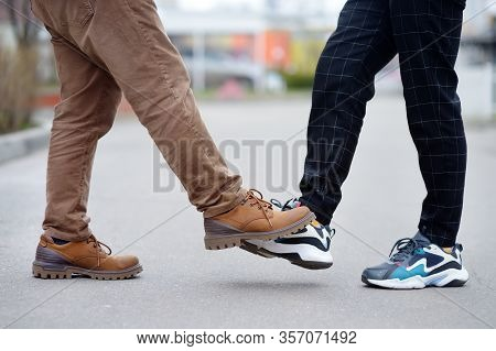 Men Greeting Each Other With Foot Instead Of Handshake. Friends Or Colleagues Touch Feet. Alternativ