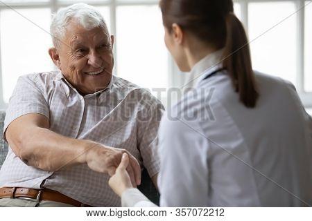 Nurse In Uniform Talking During Day Visit To Elderly Patient