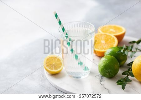 Fresh Citrus Water With Lemon Juice. Clean Water In Glass With Drinkin Straw And Lemon On Marble Bac