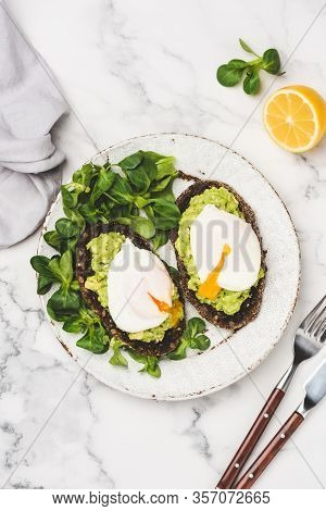 Rye Toast With Mashed Avocado, Green Salad Leaf And Poached Egg On Plate, Marble Table Background