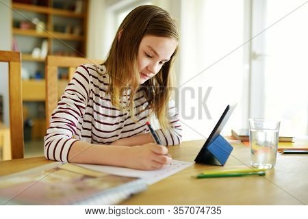 Smart Preteen Schoolgirl Doing Her Homework With Digital Tablet At Home. Education And Distance Lear