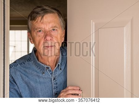 Senior Man With Looking Worried At Front Door In Case Visitors Bring Coronavirus To His Home