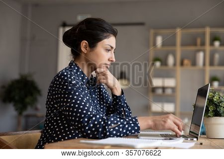 Thoughtful Indian Woman Looking At Laptop Screen, Pondering Task