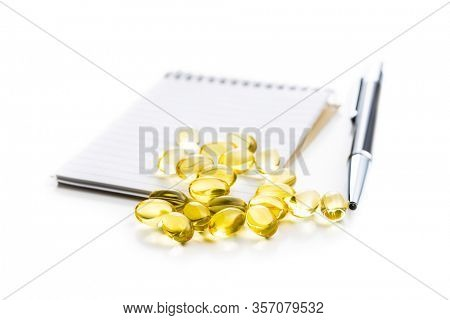Omega 3 pills. Fish oil supplement capsules and notebook isolated on white background.