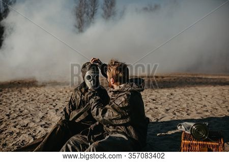 Couple In Love Sits At Outing In Nbc Protective Suits And Removes Gas Masks On Smoke Background. Con