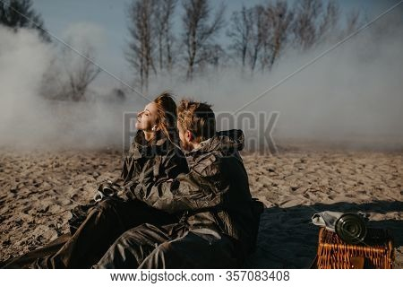 Couple In Love Sits At Outing In Nbc Protective Suits Near Removed Gas Masks On Smoke Background. Co