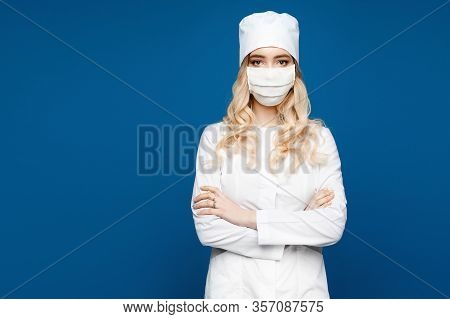 Young Woman In A White Medical Gown On A Blue Background, Isolated. Female Doctor In Medical Uniform