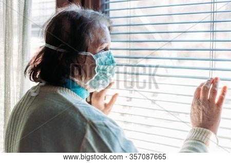Indoor Photo Of Elderly Woman With Medical, Surgical Mask On Her Face Looking Through The Window Out
