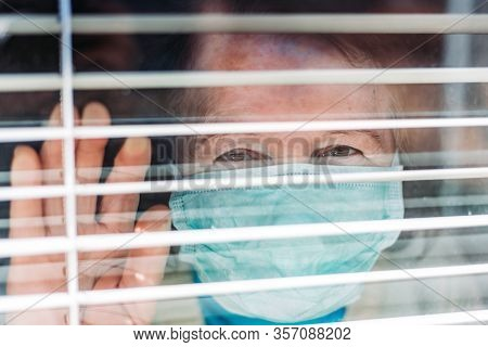 Photo Of Elderly Woman With Medical, Surgical Mask On Her Face Looking Through The Window From Insid