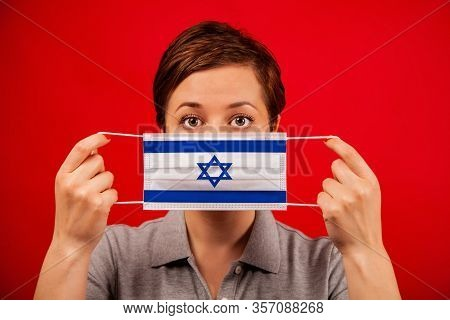 Coronavirus Covid-19 In Israel. Woman In Medical Protective Mask With The Image Of The Flag Of Israe