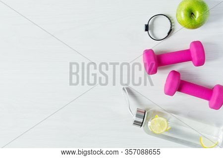 Fitness Equipment Top View With Copy Space. Fitness Concept. Dumbbells, Bottle Of Water And Fitness