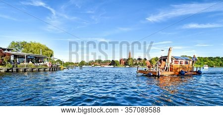 Malchow, Germany - July 9, 2017: A Man Navigates A Houseboat Across The Malchower See In The German