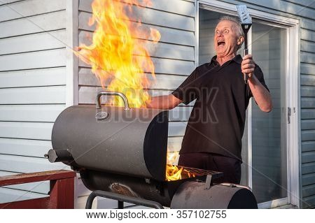 Male Reacting To A Fierce Barbecue Fire