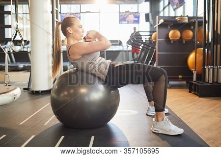 Full Length Side View At Strong Young Woman Doing Scrunches On Black Fitness Ball During Workout In